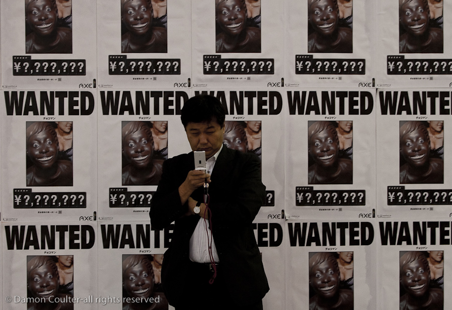 A salaryman or Japanese office worker uses a mobile phone in front of an advertising hoarding featuring wanted posters. Shibuya, Tokyo, Japan