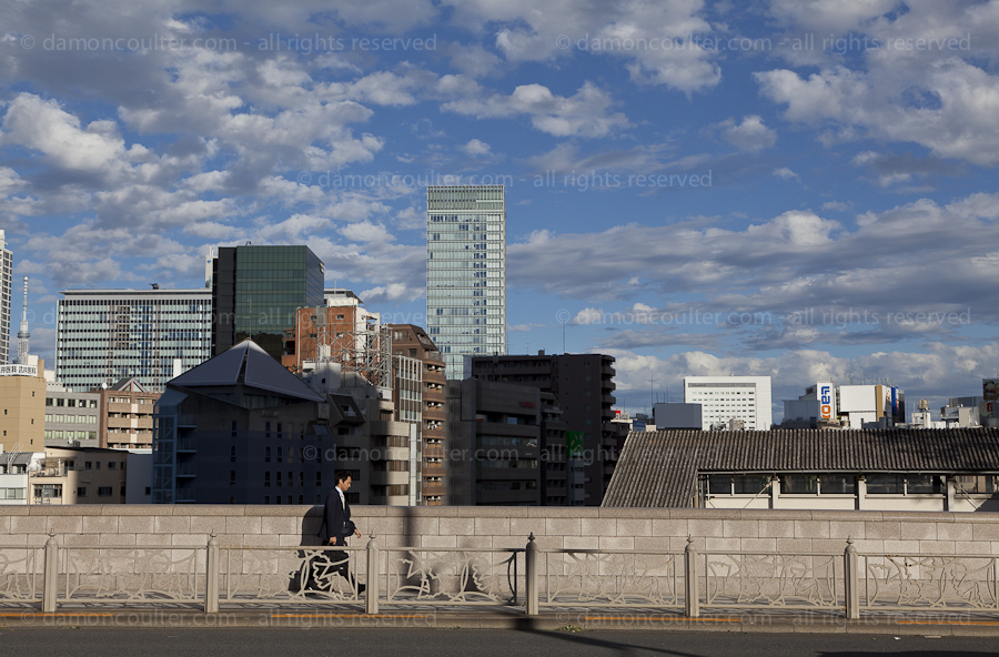A Japanese salaryman walking on a bridge near Ochanomizu station with Tokyo Skytree and other tall building behind him. Ochanomize, Tokyo, Japan. Wedneday October 16th 2013