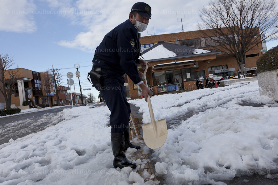 A Japanese policeman clearing snow in Tokyo after heavy snows fell on Saturday February 8th